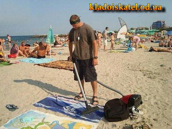мужик пылесосит пляж